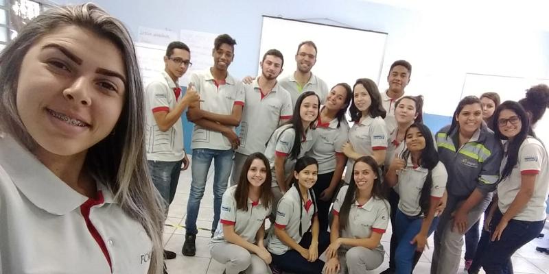 Educador Voluntário e alunos registrando participação na disciplina de Organização Empresarial.